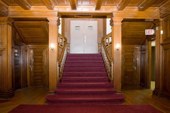 burgundy carpeted staircase surrounded by wood paneling
